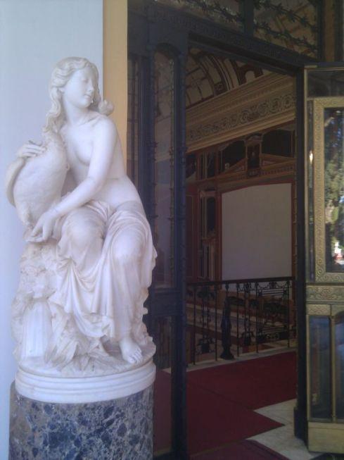 Skulptūra ar dāmu, kas spēlējas ar zosi un mazliet skats uz kāpnēm.